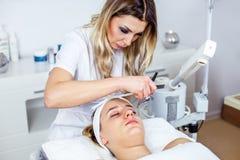 Mulheres no armário da cosmetologia O Cosmetologist está fazendo o procedimento para a moça Imagens de Stock Royalty Free