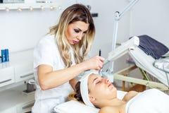 Mulheres no armário da cosmetologia O Cosmetologist está fazendo o procedimento para a moça Imagens de Stock