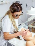 Mulheres no armário da cosmetologia O Cosmetologist está fazendo o procedimento para a moça Fotos de Stock Royalty Free