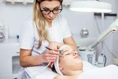 Mulheres no armário da cosmetologia O Cosmetologist está fazendo o procedimento para a moça Fotos de Stock