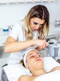 Mulheres no armário da cosmetologia O Cosmetologist está fazendo o procedimento para a moça Fotografia de Stock Royalty Free