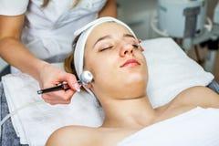 Mulheres no armário da cosmetologia O Cosmetologist está fazendo o procedimento para a moça Imagem de Stock