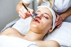 Mulheres no armário da cosmetologia O Cosmetologist está fazendo o procedimento para a moça Fotografia de Stock