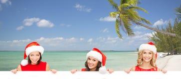 Mulheres no chapéu do ajudante de Santa com placa branca vazia Fotografia de Stock Royalty Free