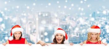 Mulheres no chapéu do ajudante de Santa com placa branca vazia Imagem de Stock
