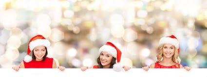 Mulheres no chapéu do ajudante de Santa com placa branca vazia Imagens de Stock