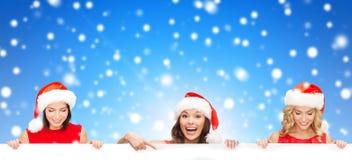 Mulheres no chapéu do ajudante de Santa com placa branca vazia Imagem de Stock Royalty Free