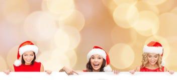 Mulheres no chapéu do ajudante de Santa com placa branca vazia Fotografia de Stock