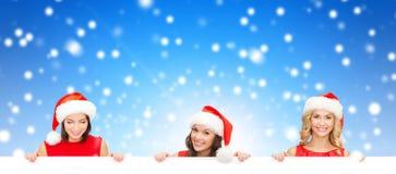Mulheres no chapéu do ajudante de Santa com placa branca vazia Fotos de Stock