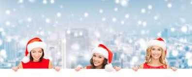 Mulheres no chapéu do ajudante de Santa com placa branca vazia Fotos de Stock Royalty Free