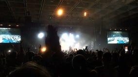 Mulheres no concerto no close up do aplauso da multidão Rocha ou concerto de batida Povos da silhueta filme