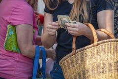 Mulheres no mercado com sacos e uma cesta da palha - menina no fron que conta dólares americanos para fora - irreconhecível fotografia de stock royalty free