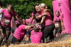 Mulheres no poço da lama no curso de obstáculo Fotos de Stock Royalty Free