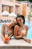 Mulheres no terno de natação elegante que relaxa perto da piscina imagens de stock