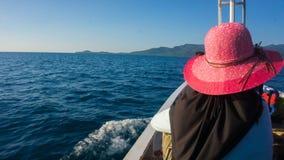 Mulheres no véu e no chapéu na parte dianteira do barco com o mar e a ilha escuros azuis na distância fotografia de stock