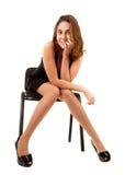 Mulheres no vestido preto na cadeira Imagem de Stock Royalty Free