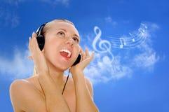Mulheres novas da felicidade nos auscultadores foto de stock royalty free