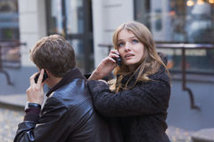 Mulheres novas e homens que falam no telefone móvel Foto de Stock Royalty Free