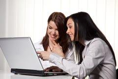 Mulheres novas em aprender um programa no portátil Foto de Stock