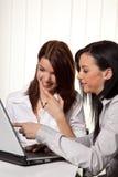 Mulheres novas em aprender um programa no portátil Imagens de Stock