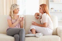 Mulheres novas encantadores que sentam-se em um sofá com copos Imagem de Stock