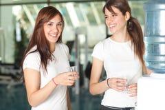 Mulheres novas na água bebendo da ginástica imagem de stock royalty free