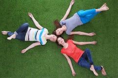 Mulheres novas que encontram-se na grama verde Jovens mulheres Imagem de Stock