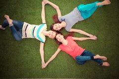 Mulheres novas que encontram-se na grama verde Jovens mulheres Fotos de Stock