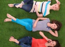 Mulheres novas que encontram-se na grama verde Jovens mulheres Fotografia de Stock Royalty Free