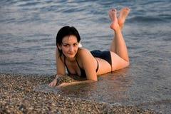 Mulheres novas que encontram-se no mar Foto de Stock Royalty Free