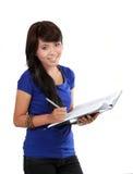 Mulheres novas que escrevem em um caderno Foto de Stock