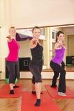 Mulheres novas que executam esticando exercícios na ginástica Fotografia de Stock Royalty Free