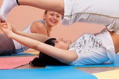 Mulheres novas que fazem exercícios de dobra Fotos de Stock