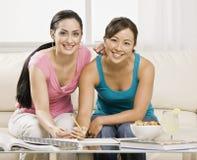 Mulheres novas que fazem trabalhos de casa Imagens de Stock Royalty Free