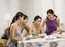 Mulheres novas que fundem para fora velas no bolo de aniversário Fotografia de Stock Royalty Free