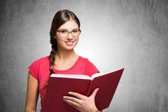 Mulheres novas que prendem um livro imagens de stock