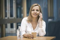 Mulheres ocasionais que usam o telefone e o café espertos da bebida Fotografia de Stock Royalty Free