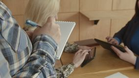 Mulheres ocupadas que usam a tabuleta ao fazer a ordem no café video estoque