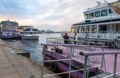 Mulheres perto do barco de turista na terraplenagem do rio de Dnieper perto do porto fluvial no quadrado de Poshtova de Kyiv, Ucr fotografia de stock royalty free