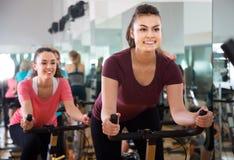 Mulheres positivas do treinamento diferente da idade em bicicletas de exercício Fotografia de Stock Royalty Free