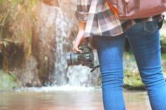 Mulheres que andam com calças de brim e sapatas da sapatilha e fundo da cachoeira, curso do conceito, delicado e foco seleto fotografia de stock