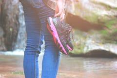 Mulheres que andam com calças de brim e sapatas da sapatilha e fundo da cachoeira, curso do conceito, delicado e foco seleto foto de stock