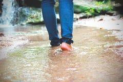 Mulheres que andam com calças de brim e sapatas da sapatilha e fundo da cachoeira, curso do conceito, delicado e foco seleto fotografia de stock royalty free