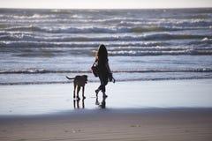 Mulheres que andam com o cão na linha de água da praia no Pacífico Foto de Stock Royalty Free