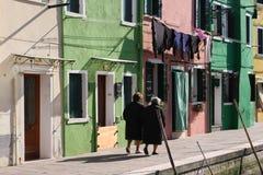 Mulheres que andam na frente das casas coloridas na margem em Burano, Veneza, Itália Fotografia de Stock Royalty Free