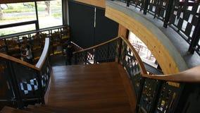 Mulheres que andam para baixo em escadas de madeira clássicas no restaurante moderno e luxuoso filme