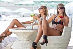 Mulheres que apreciam na barra com uns vidros de martini Fotos de Stock Royalty Free