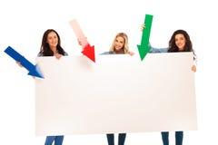 3 mulheres que apresentam a placa grande apontando setas a ela Imagens de Stock Royalty Free