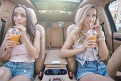 Mulheres que bebem o suco fresco com palhas foto de stock