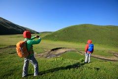 Mulheres que caminham em montanhas do beira-rio Fotografia de Stock